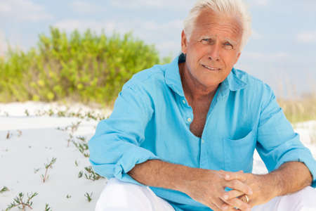 Photo pour Portrait of a worried concerned thoughtful attractive handsome senior man sitting down outside on a beach and smiling - image libre de droit