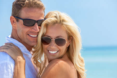Photo pour Happy and attractive man and woman couple with perfect teeth wearing sunglasses and smiling in sunshine at the beach - image libre de droit