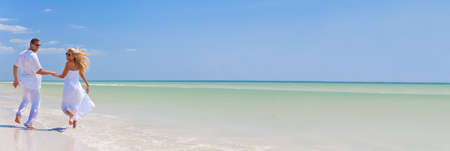 Photo pour Panorama banner happy young man and woman couple running, laughing and holding hands on a deserted tropical beach with bright clear blue sky - image libre de droit