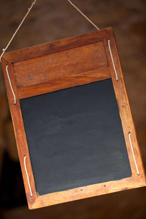 Photo for Traditional clean plain or blank wooden blackboard or chalkboard menu sign hanging in a restaurant - Royalty Free Image