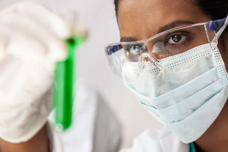 Foto de Asian medical or scientific researcher or doctor looking at a test tube of green solution in a lab or laboratory - Imagen libre de derechos