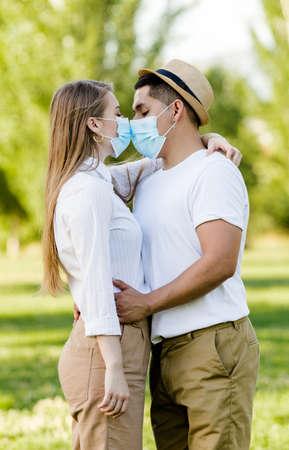 Foto de Couple with mask kissing at park - Imagen libre de derechos