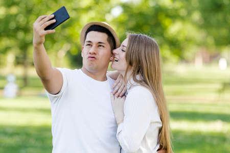 Foto de Young couple taking a selfie on their mobile in the park. Latin man and Caucasian woman - Imagen libre de derechos
