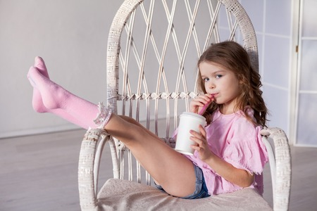 Photo for beautiful fashionable little girl sits on the couch and drinking milkshake - Royalty Free Image