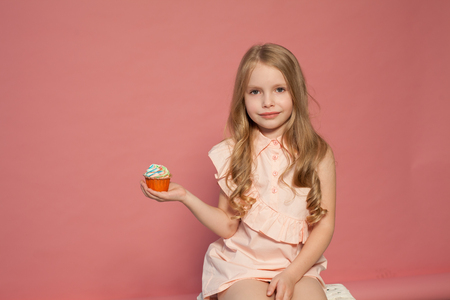 Photo pour small girl in hand holds a sweet cupcake cake candy - image libre de droit