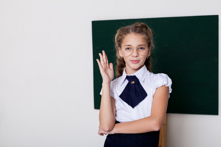 Photo pour girl school girl in glasses at the blackboard on the lesson at school - image libre de droit