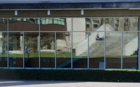 Foto de Student sitting on stairs reflected in glass wall of a building in campus n Bellingham - Imagen libre de derechos