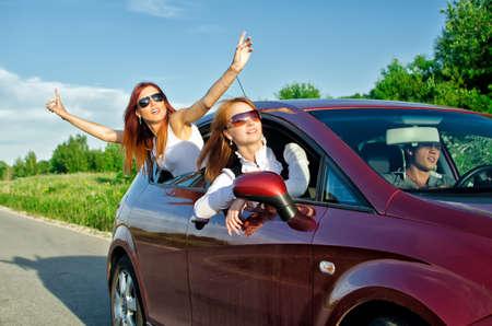 Photo pour Two pretty happy girls in the car. Concept of carefree roadtrip - image libre de droit