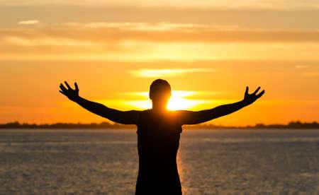 Foto de Man with arms wide open on the beach at sunrise - Imagen libre de derechos