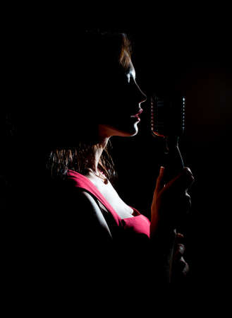 Photo for Silhouette of woman singing into vintage microphone. - Royalty Free Image