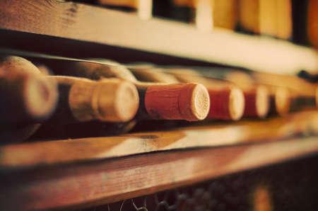Photo pour Wine bottles stacked on wooden racks. Vintage effect. - image libre de droit