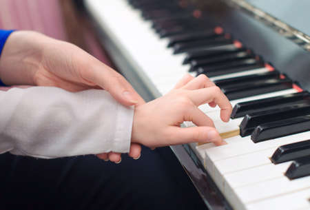 Photo pour Woman teaching little girl to play the piano. - image libre de droit