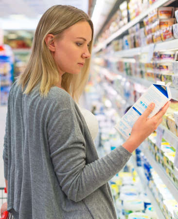 Photo for Woman choosing milk in grocery store. - Royalty Free Image