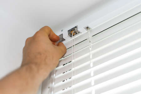 Photo pour Man installing venetian blinds on windows. - image libre de droit
