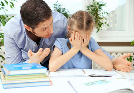 Foto de Dad is angry because his daughter don't want to do her homework. - Imagen libre de derechos