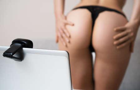 Foto de Seductive woman working as webcam model. Virtual sex. - Imagen libre de derechos