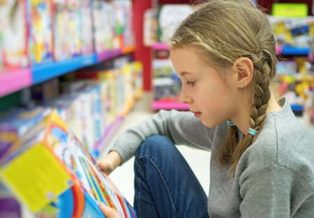 Foto de Little girl selecting toy in kids store. - Imagen libre de derechos