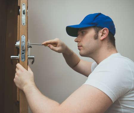Foto de Young handyman in uniform changing door lock. - Imagen libre de derechos