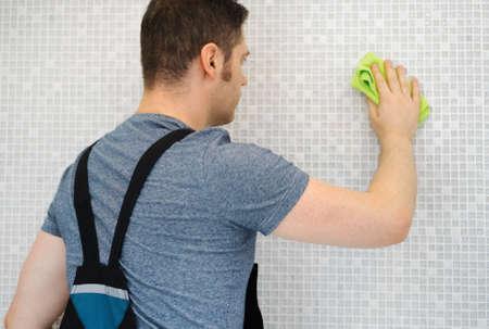 Foto de Tiler cleaning mosaic tiles in bathroom after repairs. - Imagen libre de derechos
