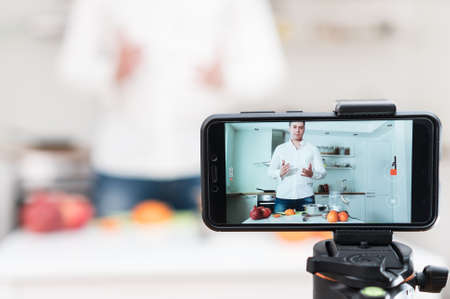 Photo for Man on the kitchen filming video. Vlogging concept. - Royalty Free Image
