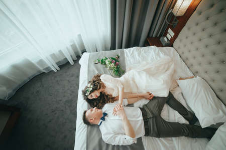 Photo for Stylish bride and groom are lying on the bed - Royalty Free Image