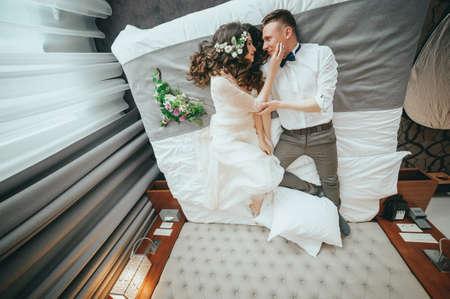 Foto de Stylish bride and groom are lying on the bed - Imagen libre de derechos