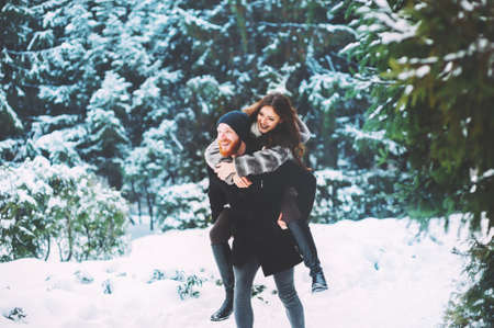 Foto de Cute young hipster couple having fun in winter park - Imagen libre de derechos