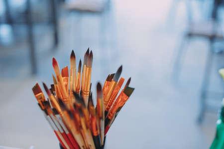 Foto de Assorted dirty painting brushes in glass flask. blue background - Imagen libre de derechos