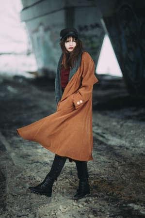 Foto de portrait of a beautiful girl in a brown coat under the bridge - Imagen libre de derechos