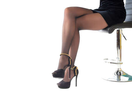 Photo pour Sexy woman wearing high heels shoes and short skirt sitting in office chair. Isolated on white - image libre de droit