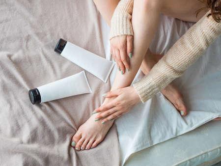 Foto de Female legs and tube of moisturiser on the bed. Skin care concept - Imagen libre de derechos