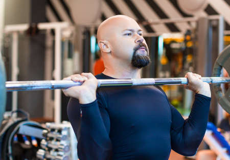 Foto de Brutal middle aged man lifting a barbell in gym. - Imagen libre de derechos