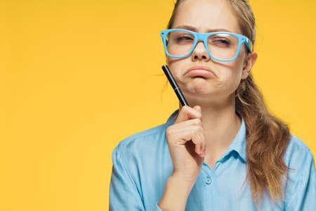 Foto de Frustrated woman, a woman in glasses holds a pen on a yellow background. - Imagen libre de derechos