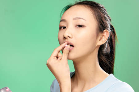 Foto de Beautiful young woman on a green background drinking a pill, asian. - Imagen libre de derechos