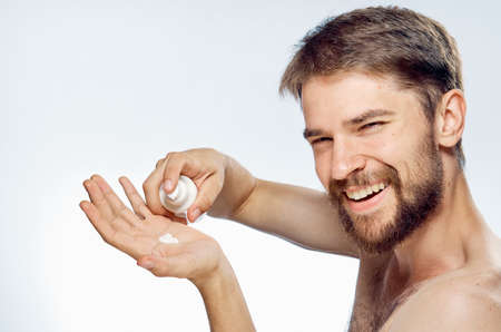 Photo pour A young guy with a beard on a white isolated background is applying foam for shaving. - image libre de droit