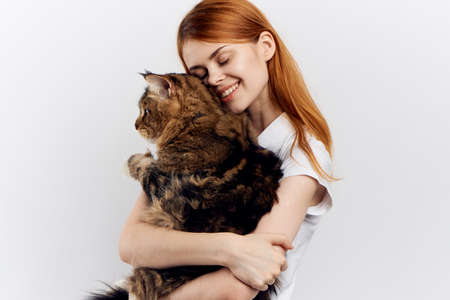 Beautiful young woman on white isolated background holds a cat, an allergy.
