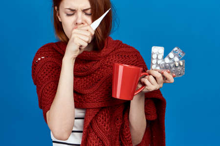 Beautiful woman on a blue background holds a mug, pills, thermometer, sickness, sick, flu.