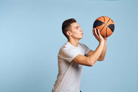 Photo pour Man with a basketball ball on a blue background sport game model white t-shirt energy - image libre de droit