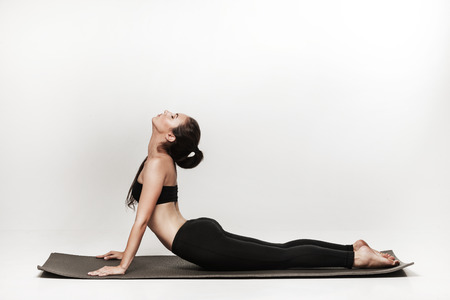 Photo pour Young fit woman at yoga class. Attractive brunette woman with pony tail practicing yoga. Healthy lifestyle and sports concept. Series of exercise poses. Isolated on white. - image libre de droit