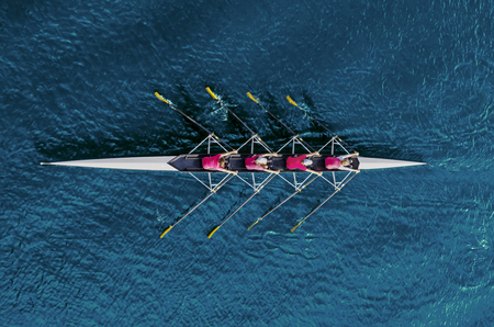 Photo pour Women's rowing team on blue water, top view - image libre de droit