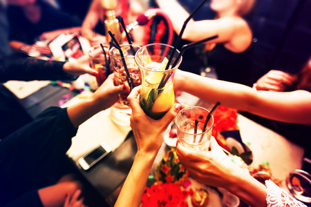 Foto de Clinking glasses with alcohol and toasting, party - Imagen libre de derechos