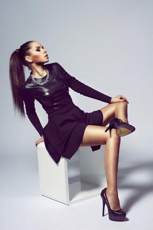 Photo pour Stylish girl posing (sitting) on white modern cube. Young woman wearing black dress and high heels. studio fashion model portrait. - image libre de droit