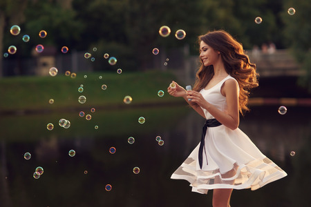 Foto de Outdoor summer portrait of young beautiful happy woman making soap bubbles in park or at nature in white dress - Imagen libre de derechos