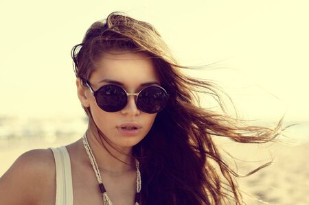 Portrait of beautiful girl in sunglasses at beach. Fashion style portrait