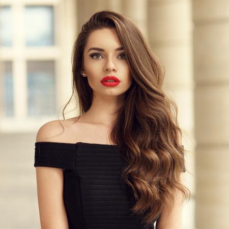 Photo pour Close up portrait of young beautiful woman with long brunette curly hair posing against architectural background - image libre de droit