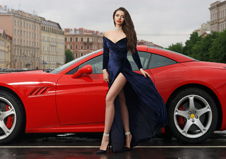 Photo pour Glamorous sexy fashionable woman with long legs in blue evening dress and long brown hair standing against red sport car at city street on overcast day - image libre de droit