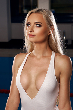 Photo pour Stunning sexy blonde woman with blue eyes dressed in white deep plunge swimsuit standing against swimming pool on background, holding metallic railing and touching her long hair with hand. Side view. - image libre de droit