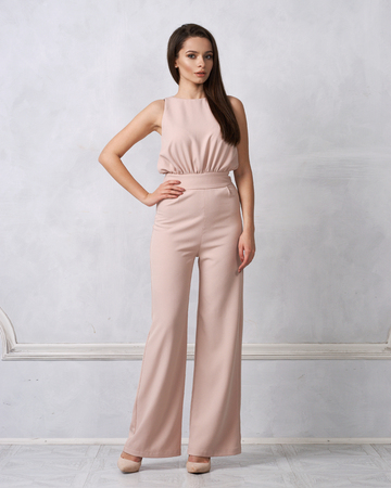 Photo pour Charming female model with long brunette hair wearing fashionable sleeveless beige jumpsuit and heeled shoes posing against white wall on background. Gorgeous woman dressed in trendy apparel. - image libre de droit