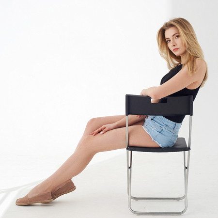 Photo for Young beautiful sexy woman in blue jeans shorts and black shirt posing and sitting on simple black chait in white studio. Fashion model with long straight hair. - Royalty Free Image