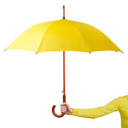 Foto de Hand holding a yellow umbrella isolated on white background - Imagen libre de derechos